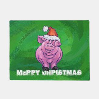 Festliches Schwein in der Weihnachtsmannmütze auf Türmatte