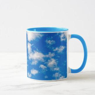 Flaumige weiße Wolken in einem blauen Himmel Tasse