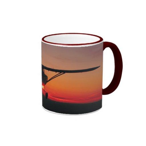 Fliegen in die Sonnenuntergang-Tasse