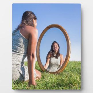 Frau, die auf dem Gras betrachtet Spiegelbild knit Fotoplatte