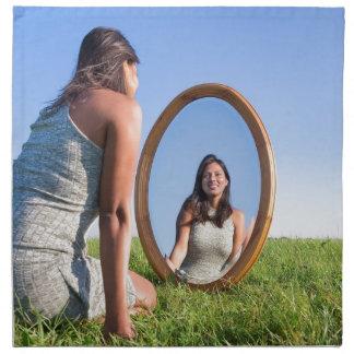 Frau, die auf dem Gras betrachtet Spiegelbild knit Stoffserviette