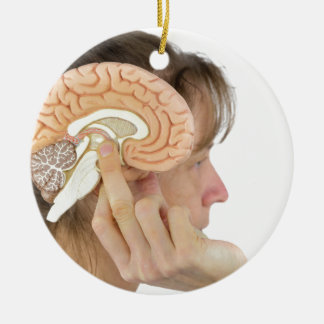Frau, die Hemisphäremodell gegen Kopf hält Keramik Ornament