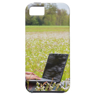 Frau, die im Frühjahr mit Wiese des Laptops sitzt Etui Fürs iPhone 5