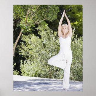 Frau, die Yoga auf Patio tut Posterdruck