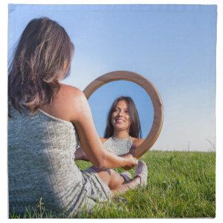 Frau in der Natur, die ihr Spiegelbild ansieht Serviette