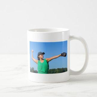 Frau mit des Handschuhs und der Kappe werfendem Kaffeetasse