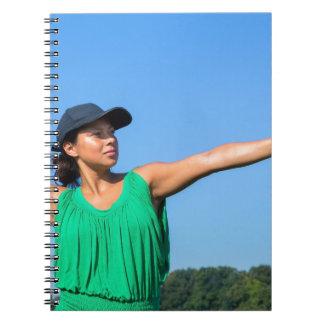 Frau mit des Handschuhs und der Kappe werfendem Spiral Notizblock