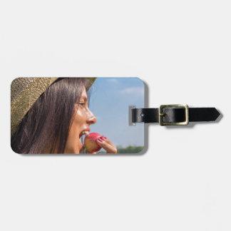 Frau mit Hut roten Apfel draußen essend Kofferanhänger