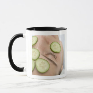 Frau mit Scheiben der frischen Gurke auf ihrem Tasse