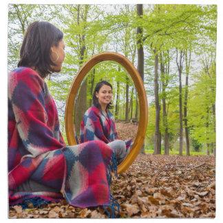 Frau sitzt mit Spiegel im Wald während des Serviette