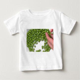 Frauenhände schälen grüne Erbsen auf einer Platte Baby T-shirt