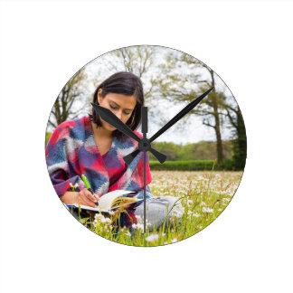 Frauenschreiben in der Wiese mit Frühlings-Blumen Runde Wanduhr