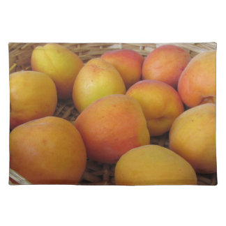 Frische Aprikosen in einem Weidenkorb auf Weiß Stofftischset