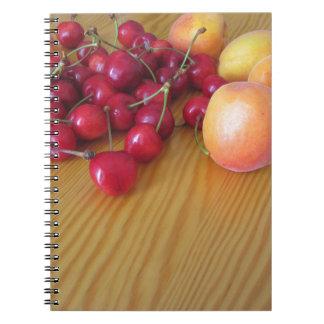 Frische Sommerfrüchte auf heller hölzerner Tabelle Notizblock