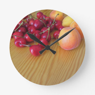 Frische Sommerfrüchte auf heller hölzerner Tabelle Runde Wanduhr
