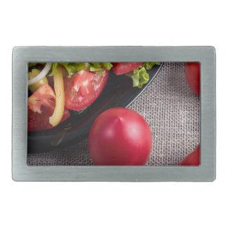 Frische Tomaten und ein Teil einer Platte mit Rechteckige Gürtelschnallen