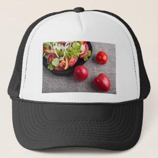 Frische Tomaten und ein Teil einer Platte mit Truckerkappe