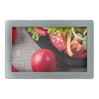 Frische Tomaten und ein Teil einer Platte Rechteckige Gürtelschnallen