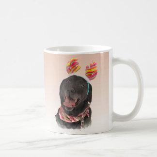 Froher schwarzer Labrador-Retriever verfolgt Tasse