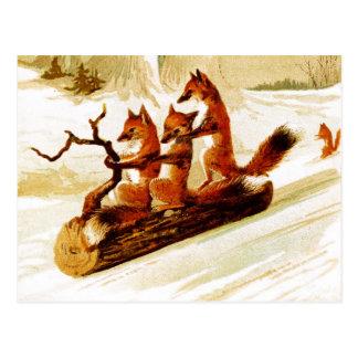 Füchse, die durch den Schnee auf einem Klotz Postkarte