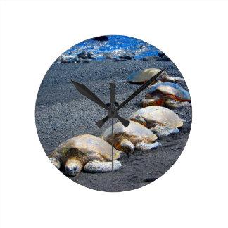 Fünf faule Schildkröten, die im Sand liegen Runde Wanduhr