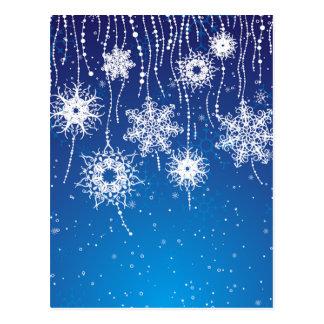 Funkelnde baumelnde Schneeflocken auf Blau Postkarte