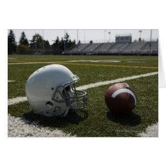 Fußball und Football-Helm auf Fußballplatz Grußkarte
