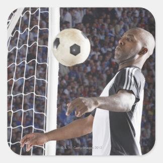 Fußballspieler, der Ball der mittleren Luft im Quadrataufkleber