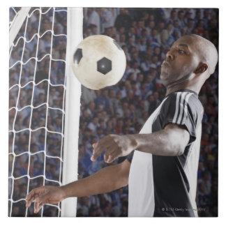 Fußballspieler, der Ball der mittleren Luft im Große Quadratische Fliese