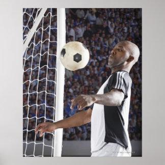 Fußballspieler, der Ball der mittleren Luft im Poster