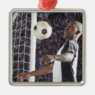 Fußballspieler, der Ball der mittleren Luft im Quadratisches Silberfarbenes Ornament