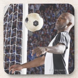 Fußballspieler, der Ball der mittleren Luft im Untersetzer