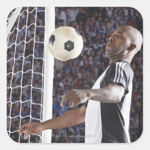 Fußballspieler, der Ball der mittleren Luft im Zie Aufkleber