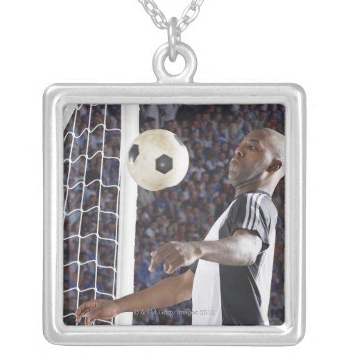 Fußballspieler, der Ball der mittleren Luft im Zie Amulett