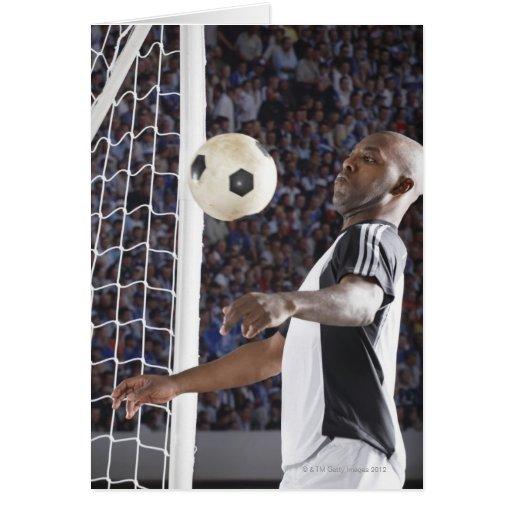 Fußballspieler, der Ball der mittleren Luft im Zie Karte