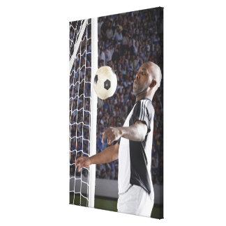 Fußballspieler der Ball der mittleren Luft im Zie Leinwand Drucke