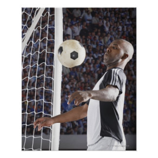 Fußballspieler der Ball der mittleren Luft im Zie Plakatdrucke