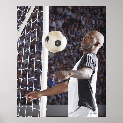 Fußballspieler, der Ball der mittleren Luft im Zie Plakatdrucke