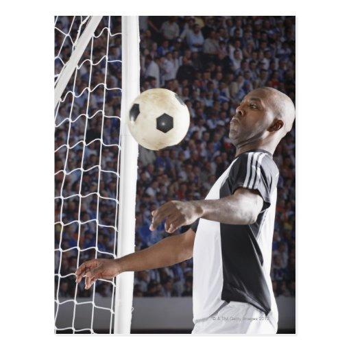 Fußballspieler, der Ball der mittleren Luft im Zie Postkarten
