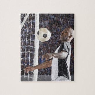 Fußballspieler, der Ball der mittleren Luft im Zie Foto Puzzle