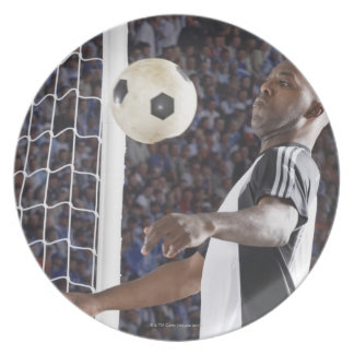 Fußballspieler, der Ball der mittleren Luft im Zie Teller