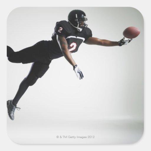 Fußballspieler, der in mittlere Luft springt, um B Stickers