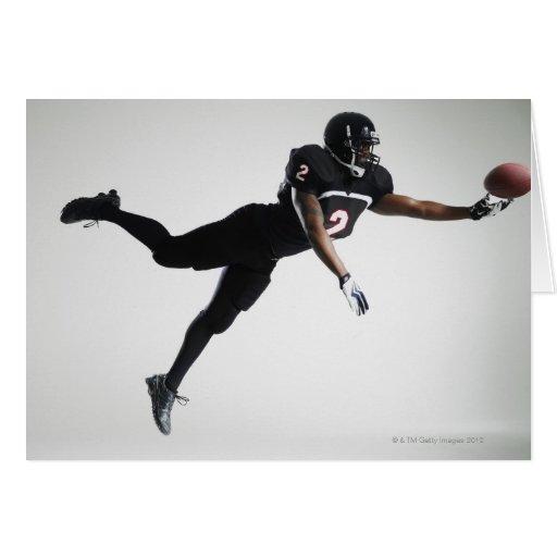 Fußballspieler, der in mittlere Luft springt, um B Karte