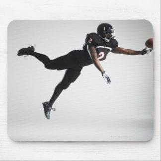 Fußballspieler, der in mittlere Luft springt, um B Mousepads