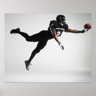 Fußballspieler, der in mittlere Luft springt, um B Plakate