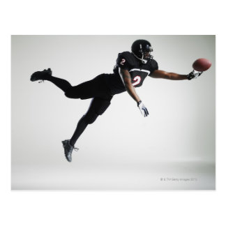Fußballspieler, der in mittlere Luft springt, um B Postkarten