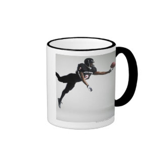 Fußballspieler, der in mittlere Luft springt, um B Kaffeehaferl
