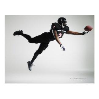 Fußballspieler, der in mittlere Luft springt, um Postkarten