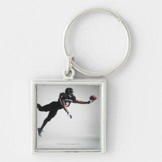 Fußballspieler, der in mittlere Luft springt, um Silberfarbener Quadratischer Schlüsselanhänger