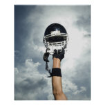 Fußballspieler, der Sturzhelm in einer Luft hält Plakat